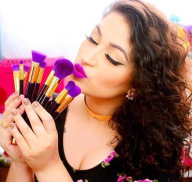 imagem de uma mulher bem maquiada segurando vários pincéis que a ajudam na maquiagem do dia a dia