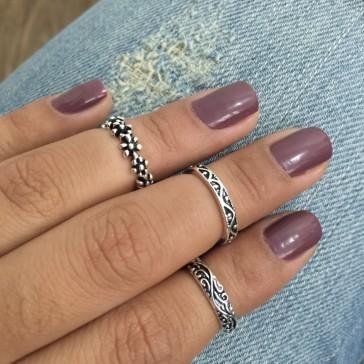 imagem ampliada de uma mão com as unhas pintadas de roxo com anéis de prata