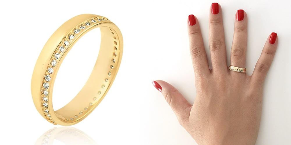 aliança de noivado e casamento dourada com pedras cravejadas ao lado de uma mão com as unhas pintadas de vermelho