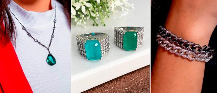 mulher com colar de pedra verde, dois anéis de pedra verde em cima de uma mesa branca, braço com duas correntes na cor prata