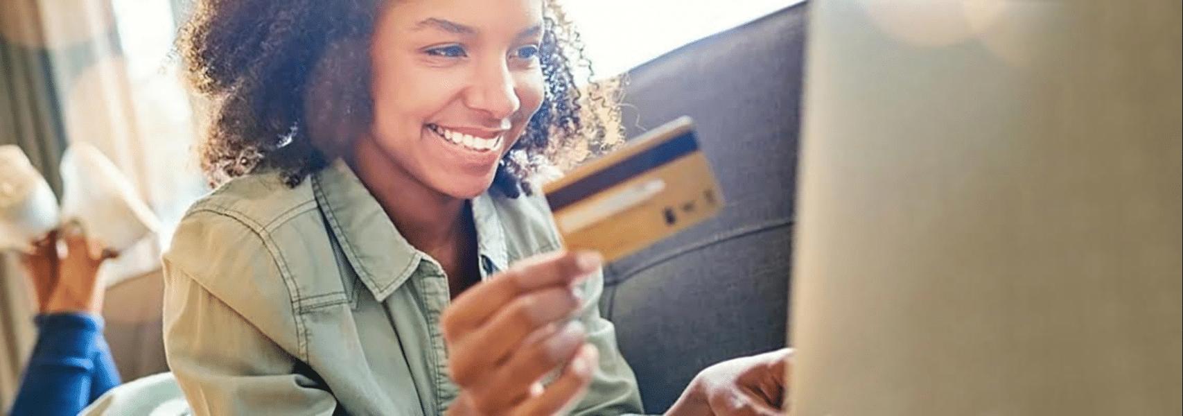 mulher deitada em sofá segurando um cartão de crédito