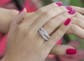 imagem ampliada de mãos femininas com anel aparador de aliança e unhas pintadas de rosa