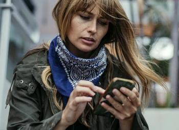 imagem de uma mulher usando seu celular em local aberto