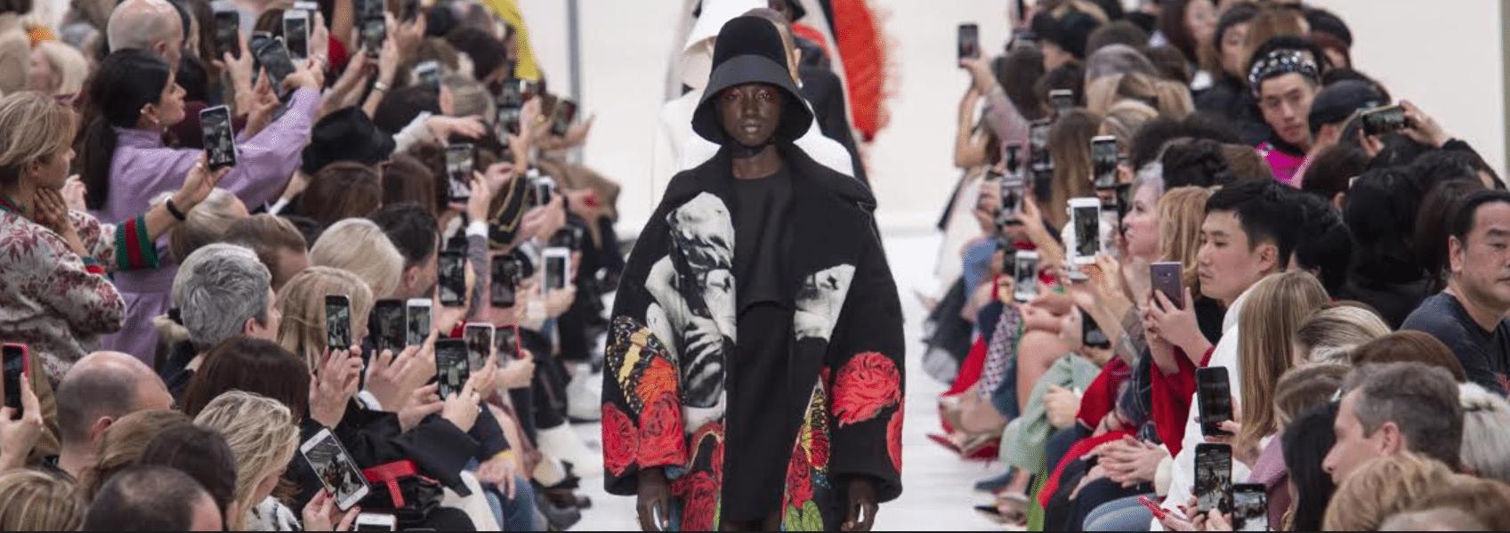 imagem de modelos vestindo sobretudo preto estampado com flores e usando um chapéu preto
