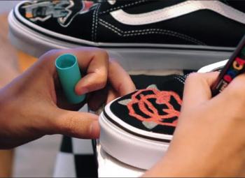 imagem ampliada de homem fazendo desenhos com uma caneta em u tênis preto