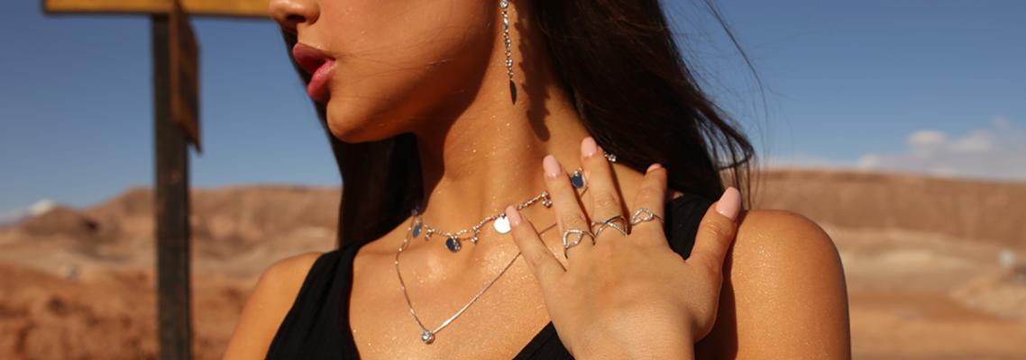 imagem de modelo em paisagem desértica usando joias minimalistas em suas mãos e pescoço