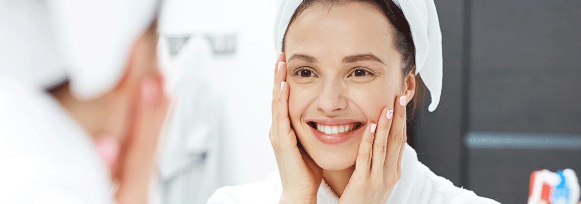 mulher usando toalha na cabeça sorri enquanto passa as mãos pelo rosto