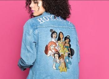 modelo de cabelos cacheado usando jaqueta jeans com desenho de frente para um fundo rosa shock