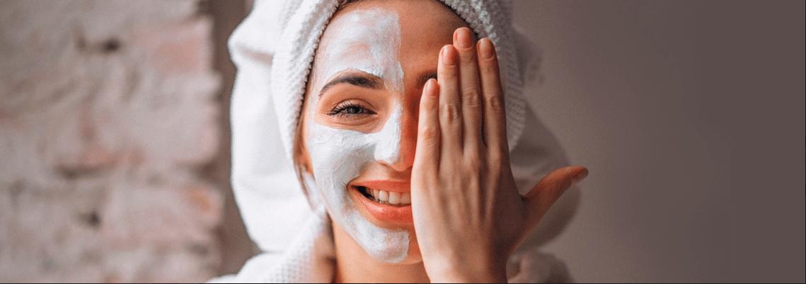 mulher com toalha na cabeça sorrindo tampando metade do rosto com a mão e com máscara facial aplicada na outra metade
