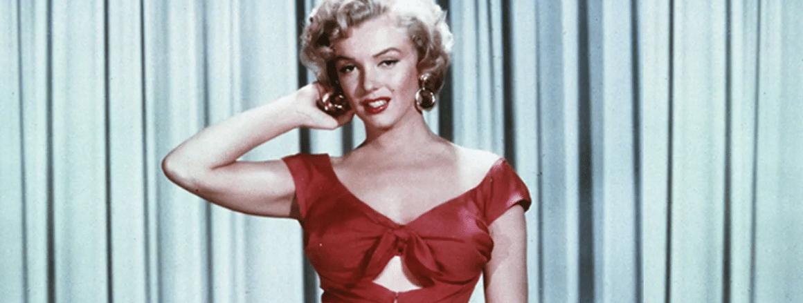 Marylin Monroe usando roupas vesmelhas de costas para cortinas azuis