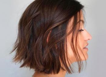 mulher de perfil com penteado short bob ao lado de uma parede azul