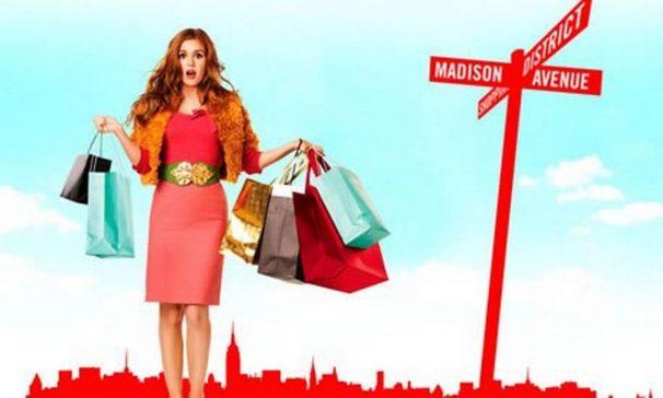 capa do filme os delírios de consumo de becky bloom com mulher usando um casaco rosa com várias sacolas de compras cheias