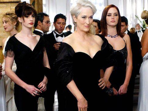 imagem do filme o diabo veste prada com anne hathaway e maryl streep usando um vestido preto dentro de um salão