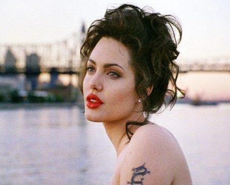 foto de angelina jolie com os cabelos presos e usando um batom vermelho vivo sentada a baira de um rio