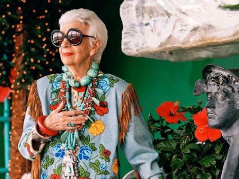 imagem do filme Iris, uma vida de estilo com idosa com roupa colorida usando óculos escuros levando sua mão ao peito