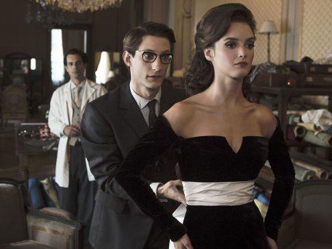 imagem do filme yves saint laurent com homem usando terno e óculos amarrando a parte de trás de um vestido de cor preta em uma mulher de costas