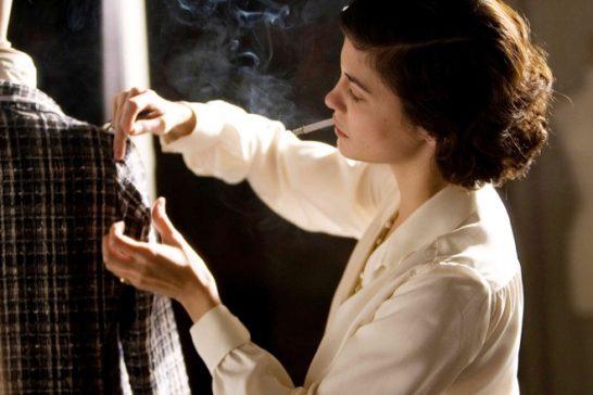 imagem do filme coco antes de chanel com mulher fumando um cigarro e prendendo partes de uma roupa