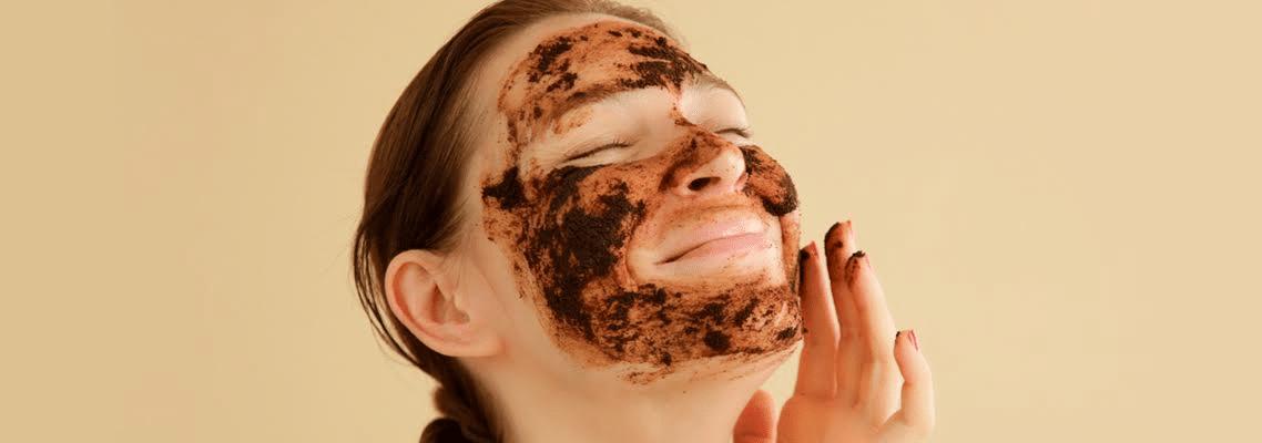 mulher sorrindo com máscara de café em seu rosto