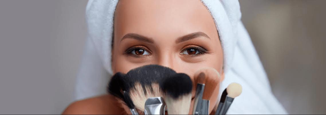 mulher com toalha na cebeça expondo pincéis de maquiagem