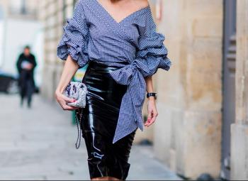 mulher usando look para baixinha com camisa azul e calça preta andando pela rua