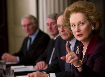 Maryl Streep em um tribunal durante o filme dama de ferro olhando para o lado e apontando para a direita