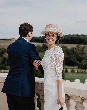 mulher sorrindo usando vestido d enoiva branco com chapéu canotier