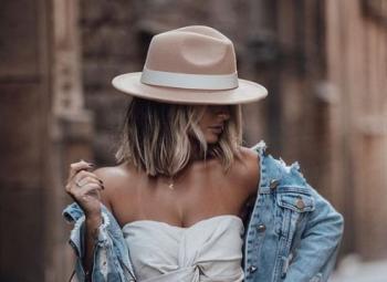 mulher posando para foto usando look com chapeu masculino e vestido branco por baixo de uma jaqueta jeans azul
