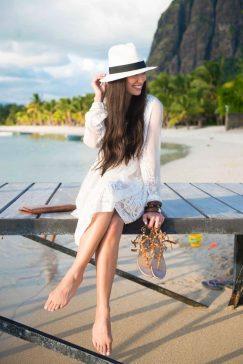 mulher sentada em um pier usando vestido branco e chapéu panamá na cor branca