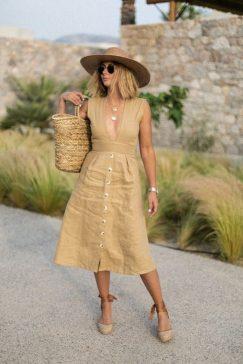 mulher loira usando looks com chapeu de praia e vestido dourado segurando uma bolsa de cesta amarela