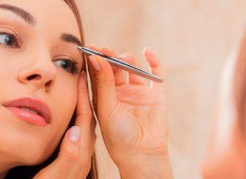mulher loira faz a sobrancelha com pinça prateada na frente do espelho