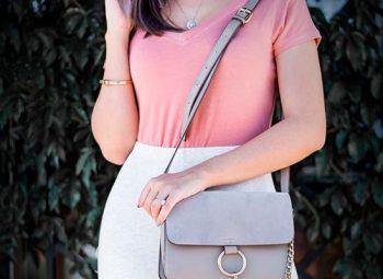 mulher usando camiseta rosa com calça creme segura uma bolsa