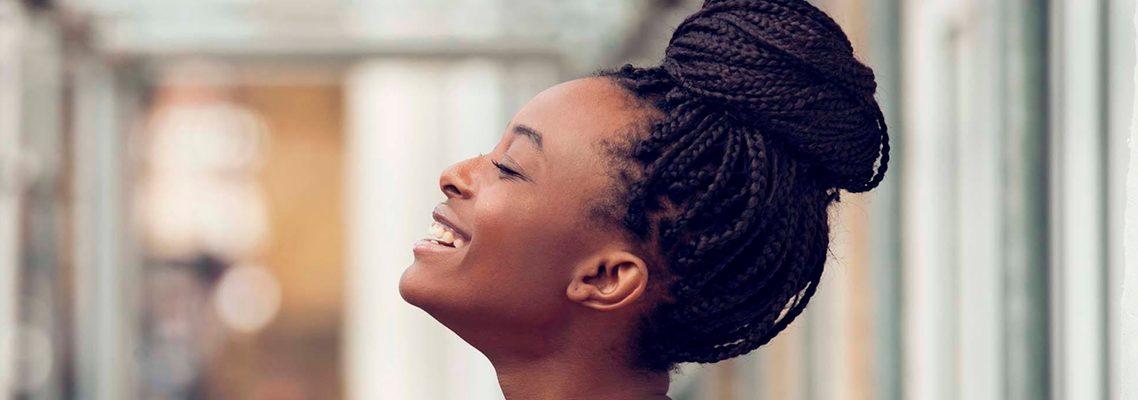 mulher negra de lado sorrindo e levando a cabeça com penteado de tranças em formato de coque