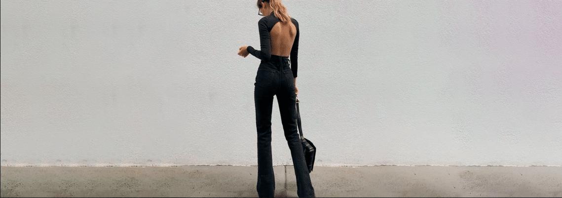 mulher alta usando conjunto de calça boca de sino, body de manga comprida aberto nas costas e bolsa