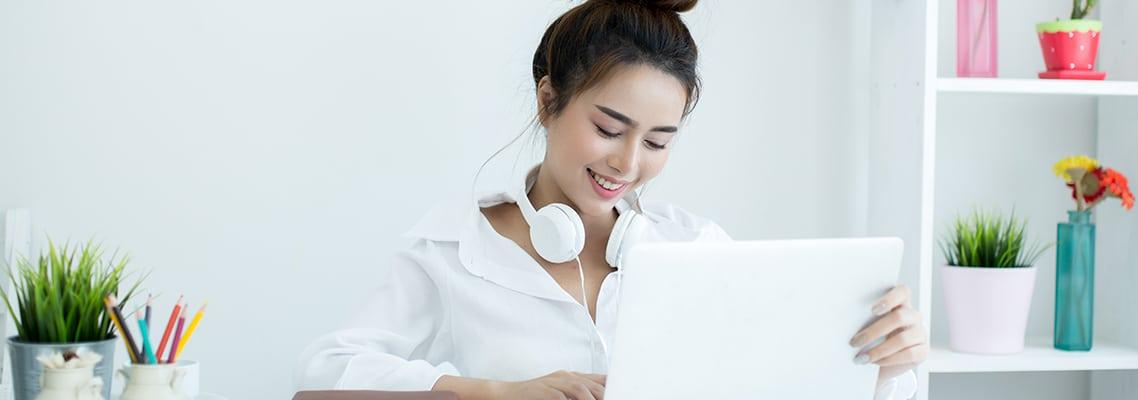 mulher com trações asiáticos com headphone no pescoço trabalhando usando look monocromático branco