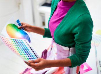 mulher com roupas verdes e roxa analisa um papel com diversas variações de cores