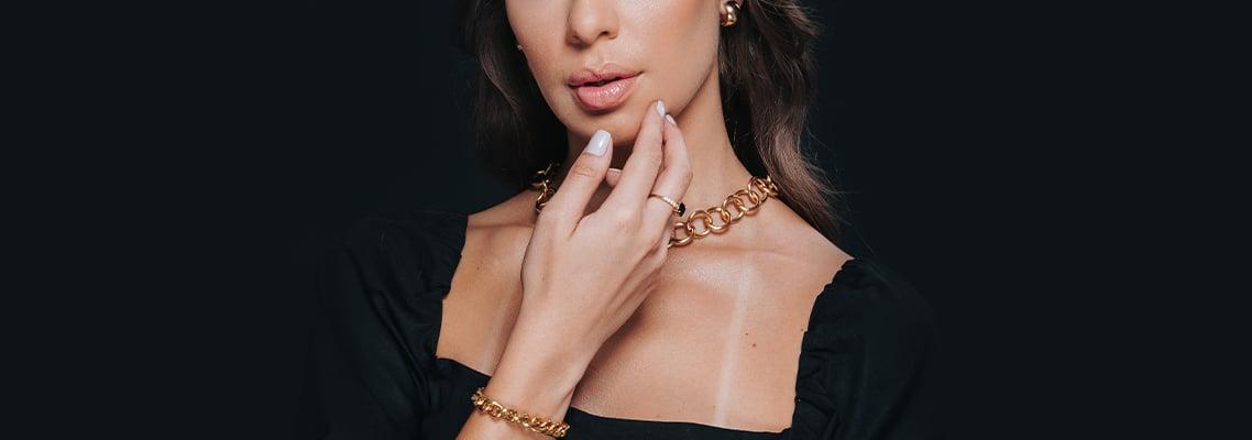 modelo de preto expondo suas joias no pulso, pescoço e orelhas